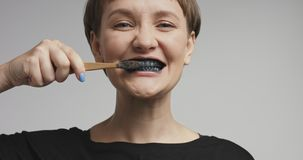 Pretty young woman brushing her teeth with black toothpaste Stock Image