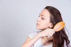 Pretty young woman brushing out her long hair Royalty Free Stock Images