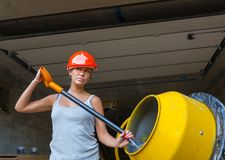 Pretty young woman builder and concrete mixer Stock Photo