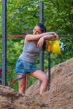 Pretty young woman builder digging a shovel Stock Image