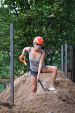 Pretty young woman builder digging a shovel Royalty Free Stock Image