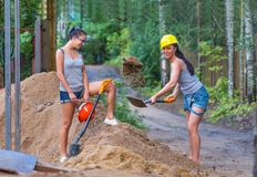 Pretty young woman builder digging a shovel Royalty Free Stock Images