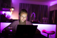 Pretty, young woman burning the midnight oil Royalty Free Stock Images