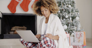 Pretty young woman buying Christmas gifts online Royalty Free Stock Image