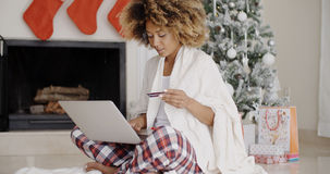 Pretty young woman buying Christmas gifts online Stock Photo