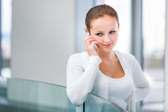 Pretty, young woman calling on her call phone, pensive, concentr. Ating, wearing bright clothes inside a modern, fresh interior (color toned image; shallow DOF Royalty Free Stock Images