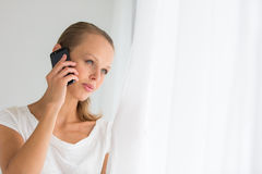 Pretty, young woman calling on her call phone. Pensive, concentrating, wearing bright clothes inside a modern, fresh interior (color toned image; shallow DOF Royalty Free Stock Photo