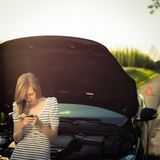 Pretty, young woman calling the roadside service royalty free stock photo