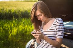 Pretty, young woman calling the roadside service stock image