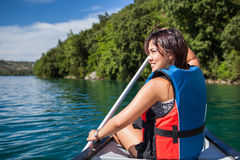 Pretty, young woman on a canoe on a lake, paddling Royalty Free Stock Photography