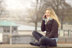 Pretty young woman chatting on her mobile. Pretty trendy young woman or student chatting on her mobile phone as she sits cross legged on a wall outdoors on a royalty free stock photos