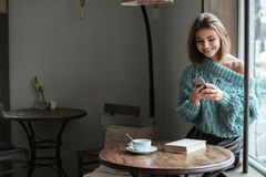 Pretty young woman chatting by her phone. Picture of pretty young woman sitting near window in cafe and chatting by her phone royalty free stock photos