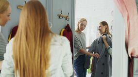Pretty young woman is checking fashionable coat in fitting room with her friend helping her to appraise garment. They. Are talking, gesturing and looking at stock video