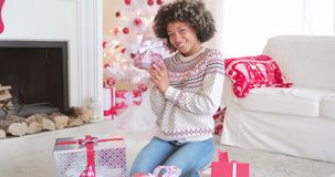 Pretty young woman checking her Christmas gifts stock video