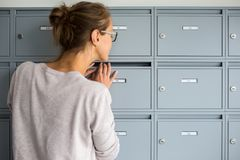 Pretty, young woman checking her mailbox Royalty Free Stock Images