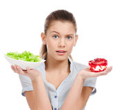 Pretty young woman choice salad or cake. Isolated Royalty Free Stock Photo