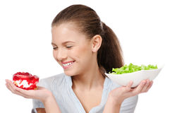 Pretty young woman choice salad or cake. Isolated. Pretty young woman choice lettuce salad or cake. Isolated on the white background Royalty Free Stock Photos