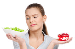 Pretty young woman choice salad or cake. Isolated Stock Image