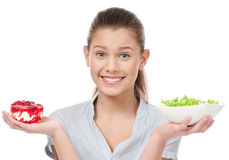 Pretty young woman choice salad or cake. Isolated. Pretty young woman choice lettuce salad or cake. Isolated on the white background Royalty Free Stock Photo