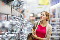 Pretty young woman choosing a bathroom/kitchen tap in a home fur Royalty Free Stock Image