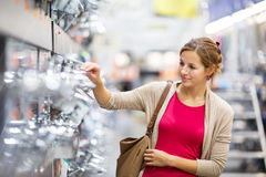 Pretty young woman choosing a bathroom/kitchen tap in a home fur Royalty Free Stock Photos