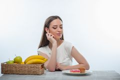 Pretty young woman is choosing between fruits and Stock Photography