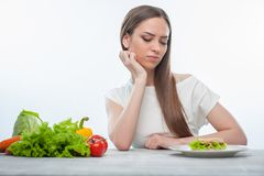 Pretty young woman is choosing between healthy and Stock Image