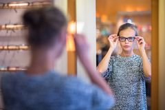 Pretty, young woman choosing new glasses frames Royalty Free Stock Images