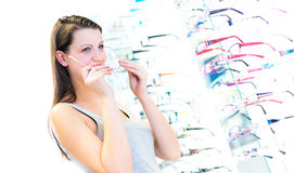 Pretty, young woman choosing new glasses frames Royalty Free Stock Photo