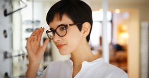 Pretty young woman is choosing new glasses at optics store Stock Photo