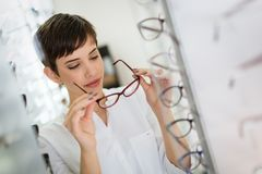 Pretty young woman is choosing new glasses at optics store. To correct eyesight Royalty Free Stock Images