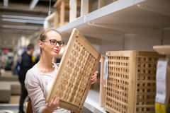 Pretty, young woman choosing the right furniture Stock Photos