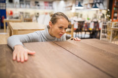Pretty, young woman choosing the right furniture Stock Images