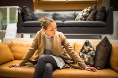 Pretty, young woman choosing the right furniture. For her apartment stock image