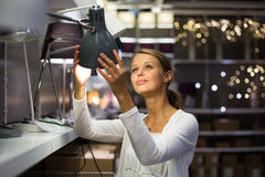 Pretty, young woman choosing the right lamp for her apartment Stock Images