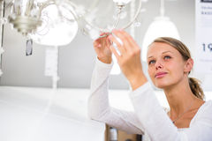 Pretty, young woman choosing the right light for her apartment Stock Image
