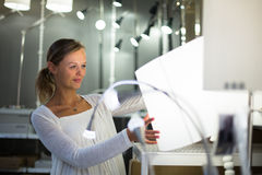 Pretty, young woman choosing the right light for her apartment Royalty Free Stock Photography