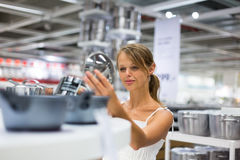 Pretty, young woman choosing a the right pot Royalty Free Stock Photo