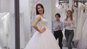 Pretty young woman is choosing a wedding dress in the shop and the shop assistant is helping her. Group of Girls in. Pretty young woman is choosing a wedding stock video footage