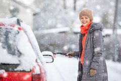 Pretty, young woman cleaning her car from snow stock photography