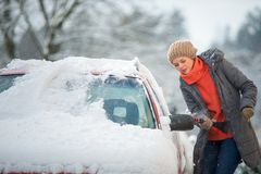 Pretty, young woman cleaning her car from snow royalty free stock image