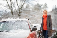 Pretty, young woman cleaning her car from snow stock photo