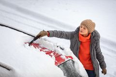 Pretty, young woman cleaning her car from snow stock image