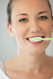 Pretty young woman cleaning her teeth Stock Photography