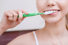 Pretty young woman cleaning her teeth Royalty Free Stock Images