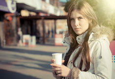 Pretty young woman in coat holding paper cup on Stock Photos