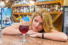 Pretty young woman with a cocktail. In bar stock images