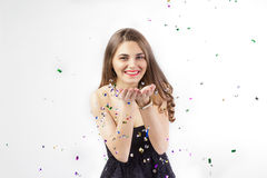 Pretty young woman with confetti smiles Royalty Free Stock Photo