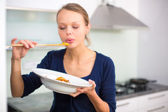 Pretty, young woman cooking a diner in a modern kitchen. Tasing the food she made Stock Images