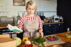 Pretty Young Woman Cooking in Kitchen. Portrait of young blonde woman cooking in kitchen making salad and  using cookbook, copy space Stock Photos